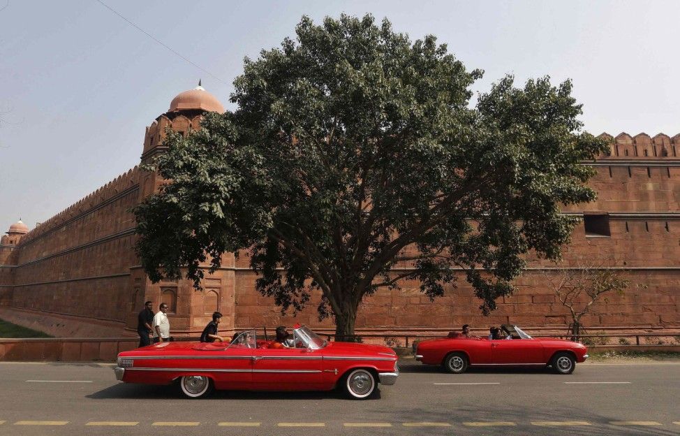 Participants drive their cars during a vintage car rally in front of the historic Red Fort in Delhi