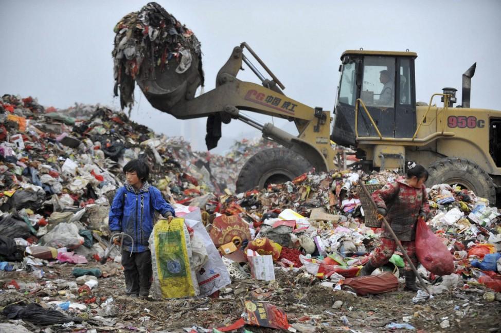 Children sort garbage at a dump site in Guiyang