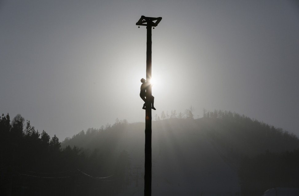 A man climbs up a 13-metre-high wooden pole during Maslenitsa celebrations at the Bobrovy Log ski resort in Krasnoyarsk