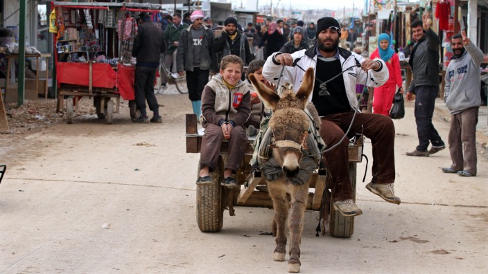 Syrian refugees use a donkey carriage for transportation after recent stormy weather and snowfalls at Zaatari Syrian refugee camp in Mafraq, Jordan, Saturday, Feb. 21, 2015. (AP Photo/Raad Adayleh)