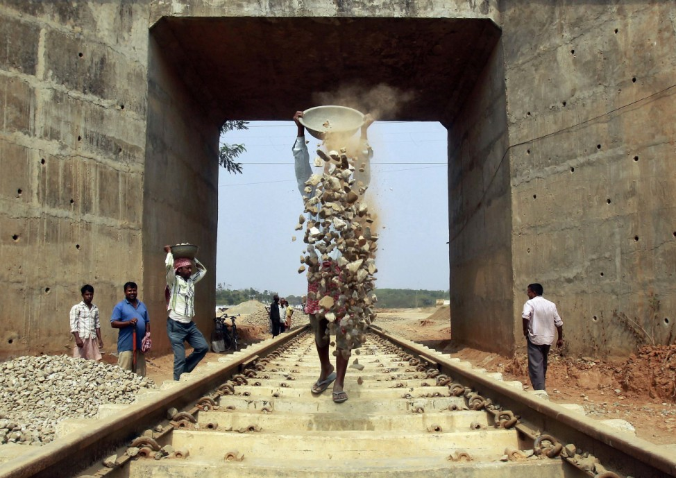 Labourers work at the installation site of a new railway track on the outskirts of Agartala