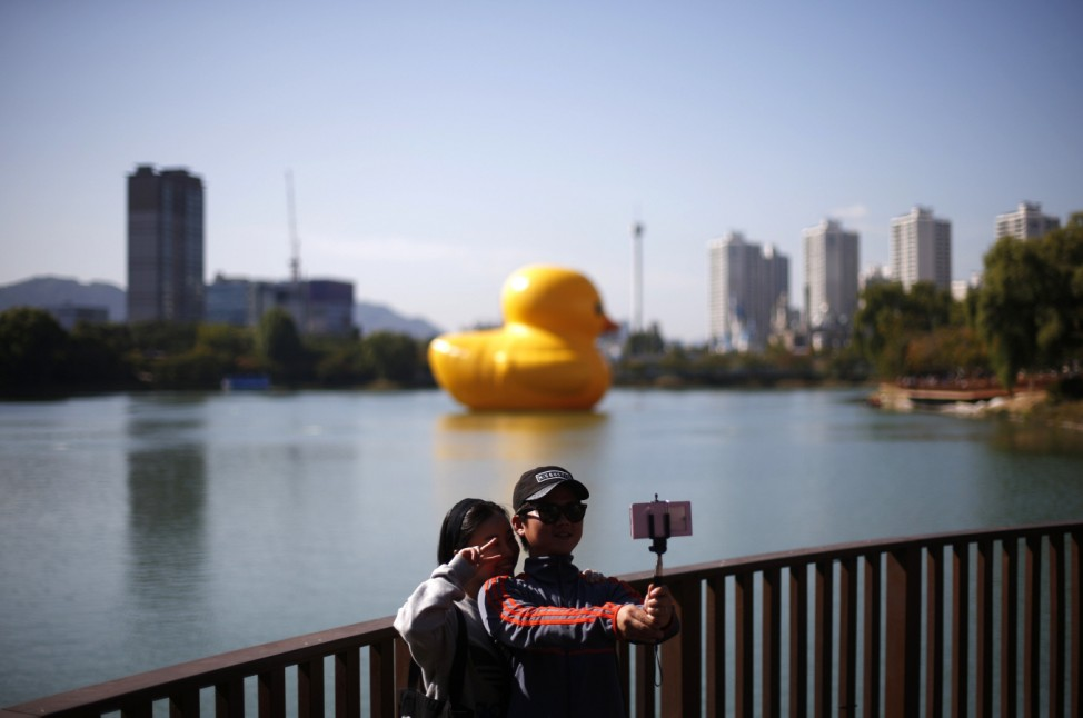 A couple takes a 'selfie' in front of the giant inflatable Rubber Duck installation by Dutch artist Florentijn Hofman floating in Seokchon Lake as part of promotional events for the Lotte World Tower in Seoul