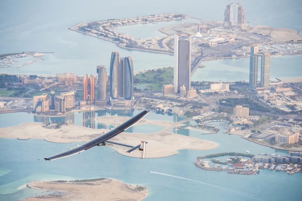 The Solar Impulse 2, a solar-powered plane, flies over the landscape of Abu Dhabi