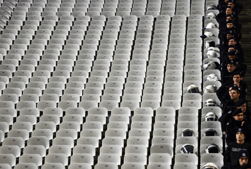 Policemen stand beside empty seats before the Europa League round of 32 second leg soccer match between Besiktas and Liverpool in Istanbul