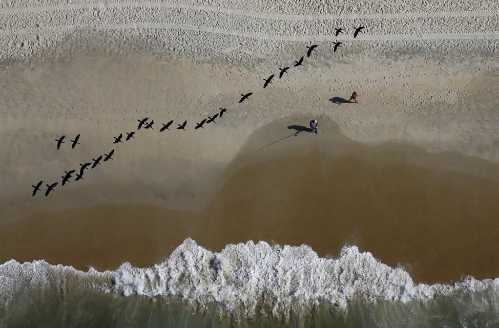 A fisherman casts his line as birds fly over the Sao Conrado beach in Rio de Janeiro