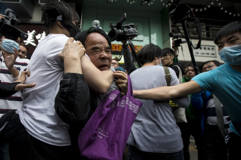 Protesters restrain a man (C) who allegedly beat other fellow protesters during a demonstration against mainland traders, at Yuen Long in Hong Kong