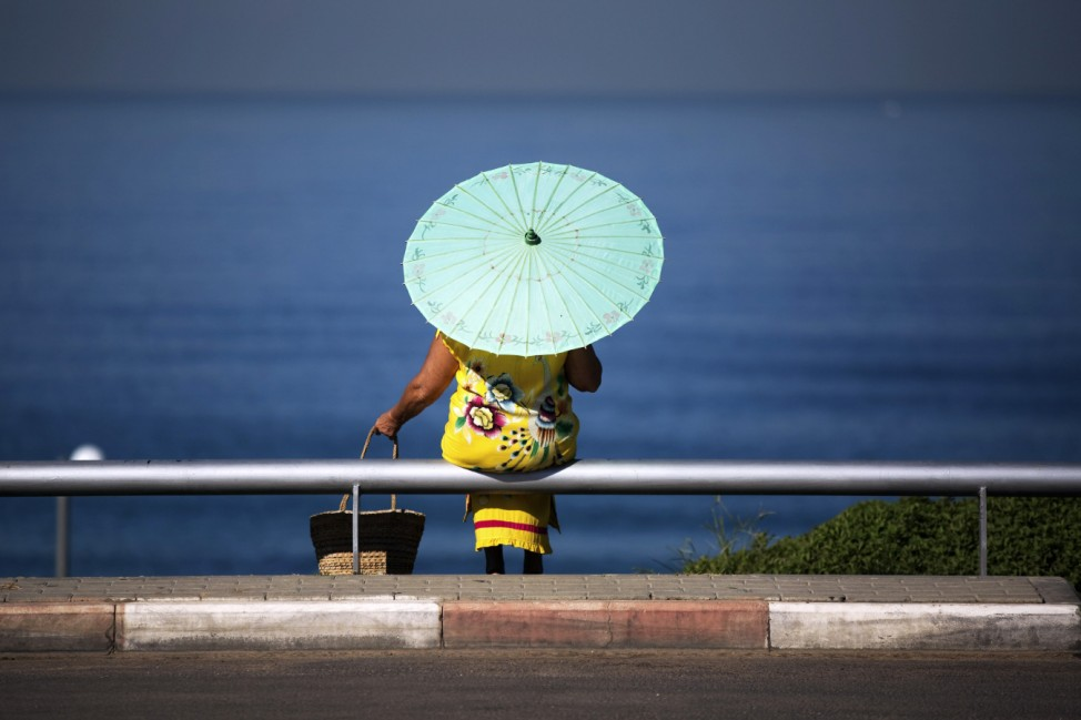A woman with a parasol sits overlooking the Mediterranean Sea near a beach in Tel Aviv