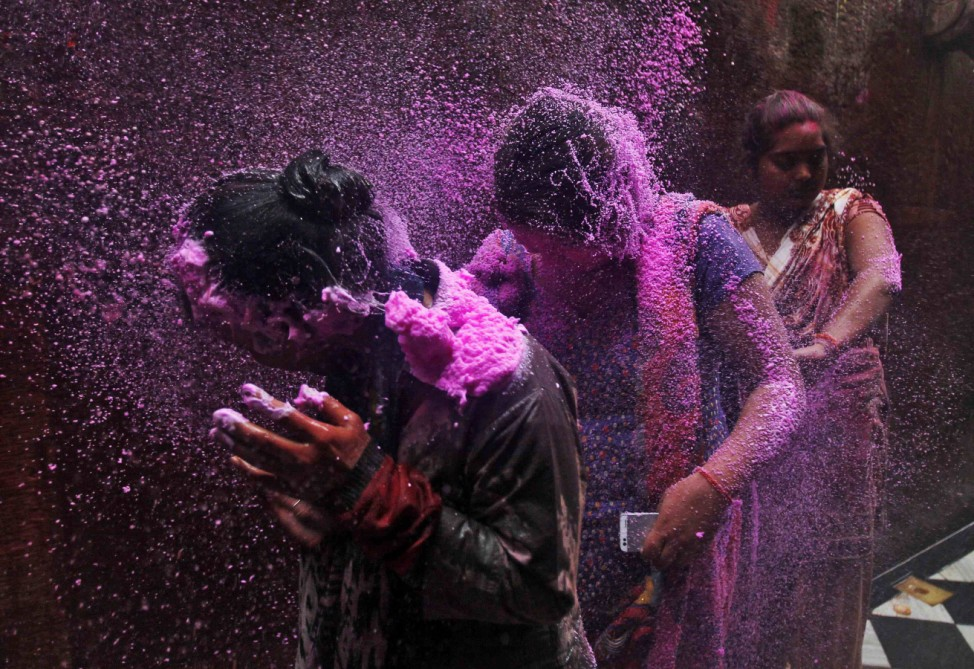 People spray coloured foam on women as they walk in a lane near the Bankey Bihari temple during Holi celebrations in Vrindavan