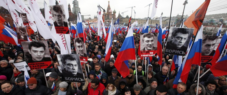 People march behind a banner to commemorate Kremlin critic Boris Nemtsov, who was shot dead on Friday night, in central Moscow