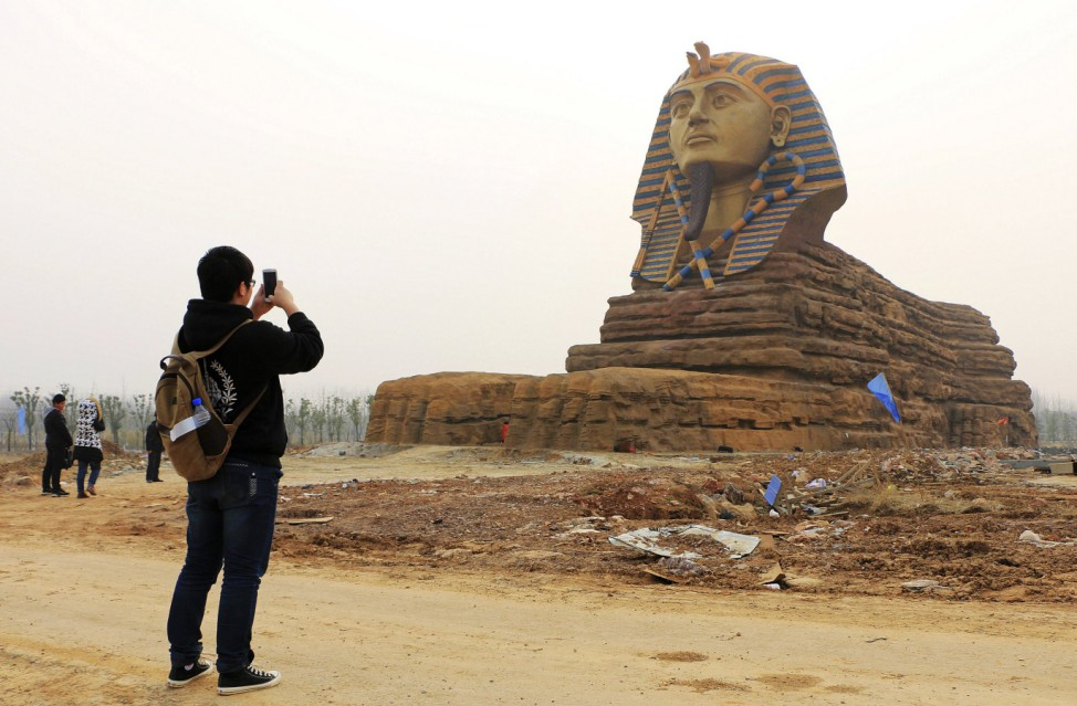 A man takes pictures of a full scale replica of the sphinx, which is part of an unfinished movie and animation tourism theme park, in Chuzhou