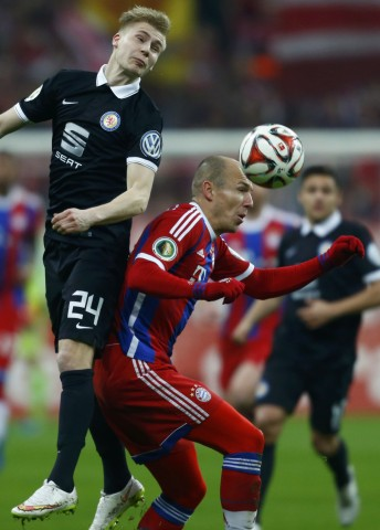 Munich's Robben and Braunschweig's Sauer jump for a header during their DFB Pokal soccer match in Munich