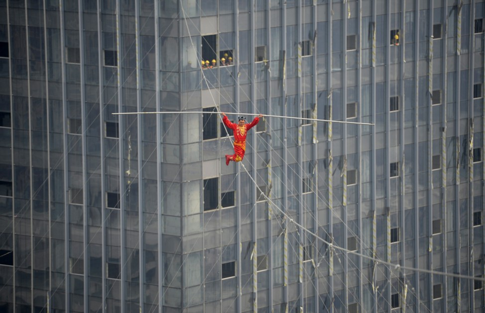 An acrobat crosses a tightrope with his knees over the Wanda Plaza in Taiyuan