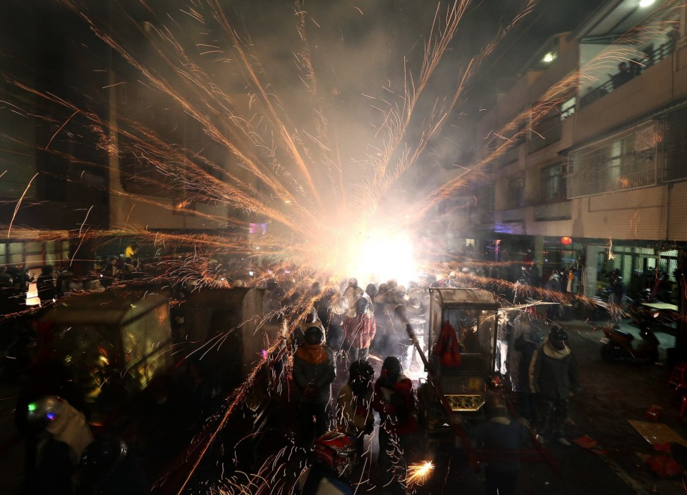 Firecrackers go off next to people during the Beehive Rockets Festival, ahead of the Chinese Lantern Festival in Tainan