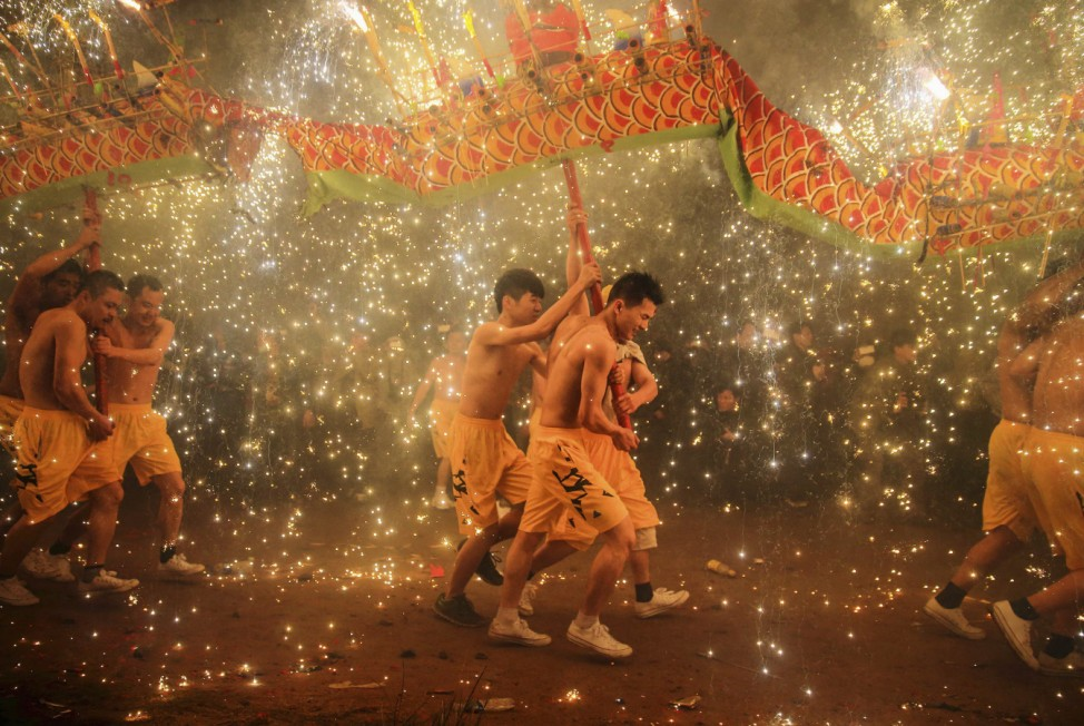 People perform a fire dragon dance in the shower of molten iron spewing sparks to celebrate the Lantern Festival, in Meizhou