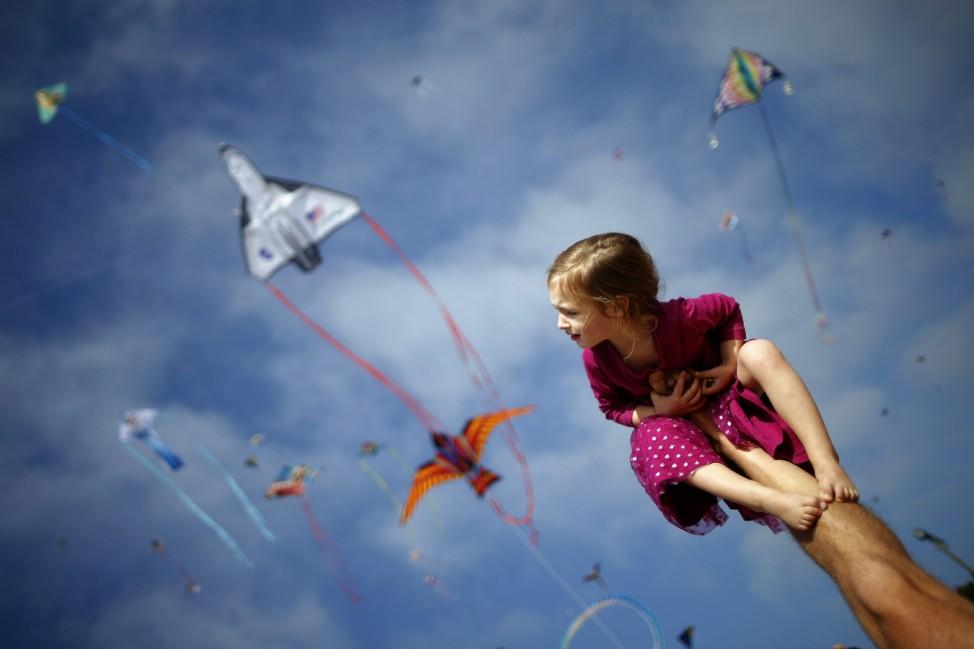 Klonoski sits on her father's leg at a kite festival in Redondo Beach