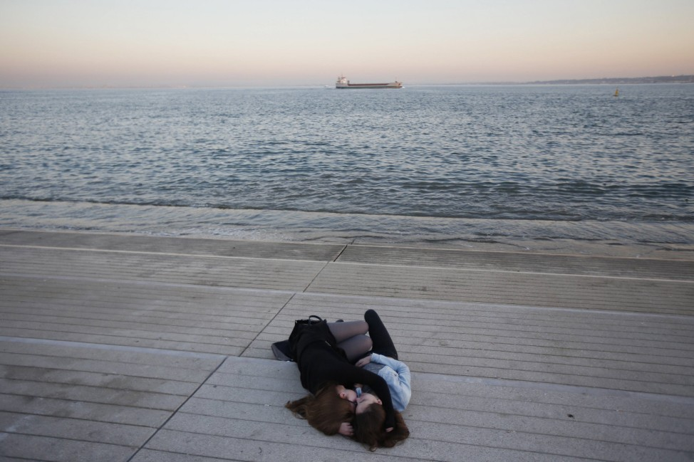 Two women hug as they sleep at a balustrade in downtown Lisbon
