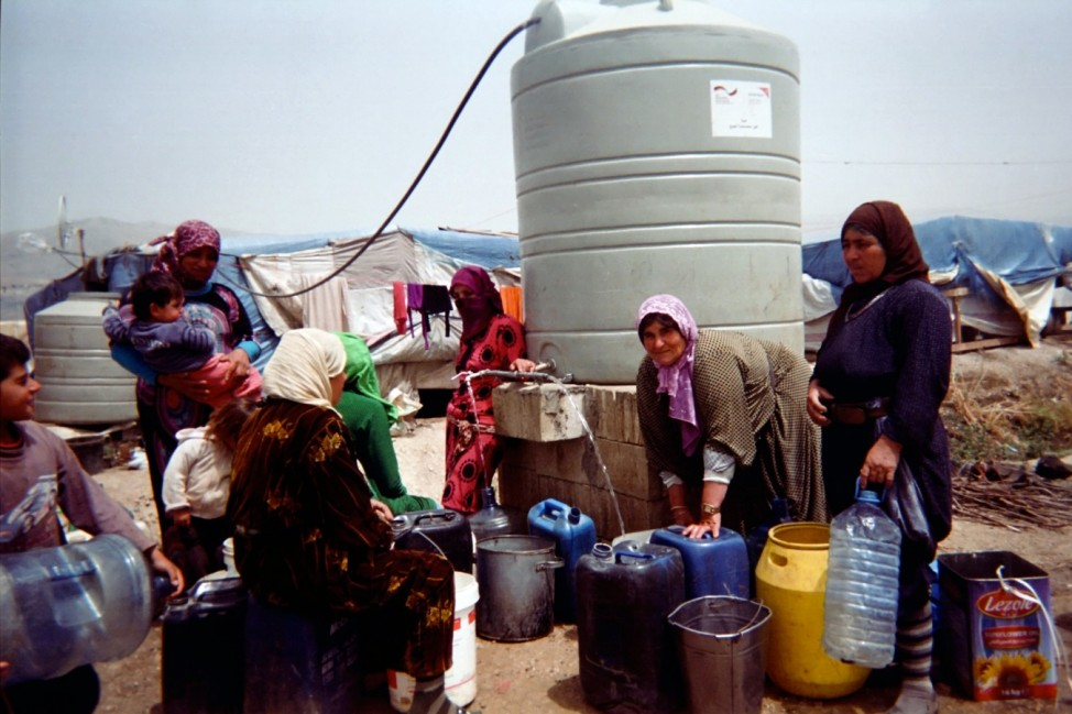 Riham, 11 years, from Homs, lives in an informal settlement in Bekaa Valley. Riham portrayed with her disposable camera a group of Syrian women carrying empty plastic buckets, containers and bottles to be filled with water from a nearby water tank.  He is