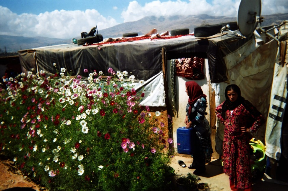 Rana 10 years, from Idleb, lives in an informal settlement in Bekaa Valley. Rana photographed with her disposable camera two Syrian woman standing in front of a tent covered with flowers. Even in such conditions Syrian refugees have planted flowers in fro