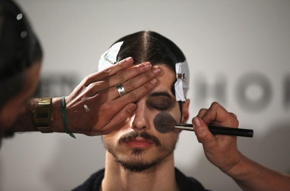 A model is prepared backstage before Sangue Novo show during Lisbon Fashion Week