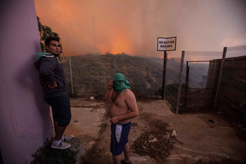 A man covers his face while a forest fire burns the hills of Valparaiso city