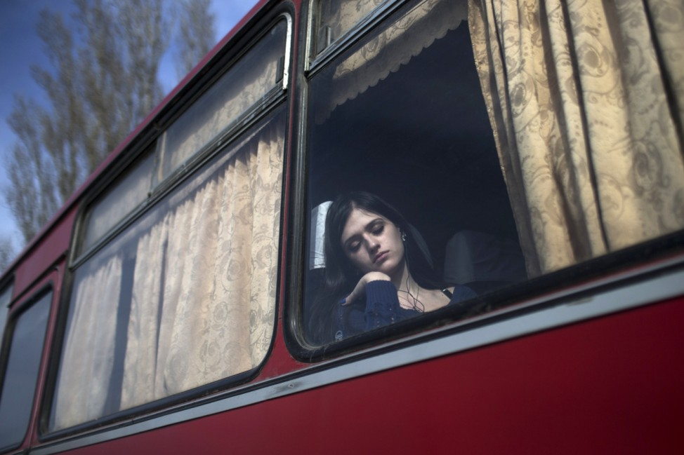 A woman takes a nap inside a bus while waiting to cross the Uspenka border crossing between Ukraine and Russia, southeast from Donetsk