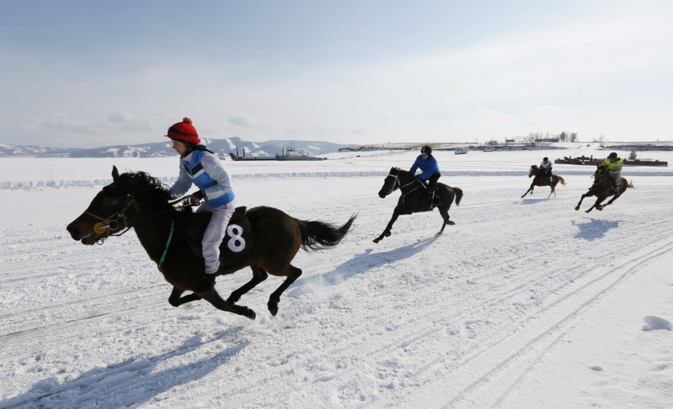 Riders compete on frozen Yenisei River during Ice Derby amateur horse race near settlement of Novosyolovo