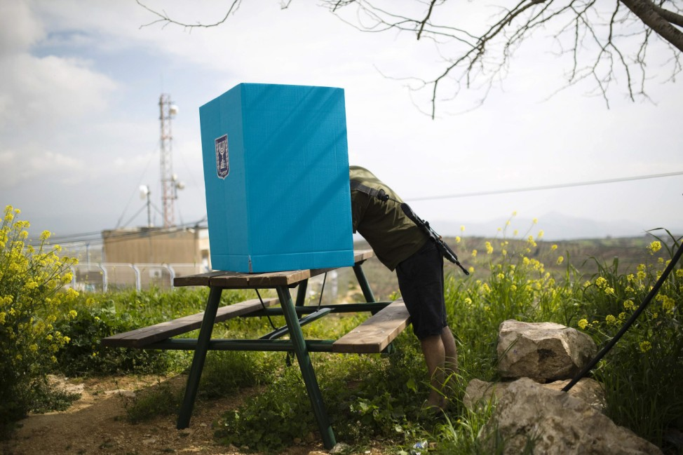 An Israeli soldier casts his ballot for the parliamentary election behind a mobile voting booth in Migdalim