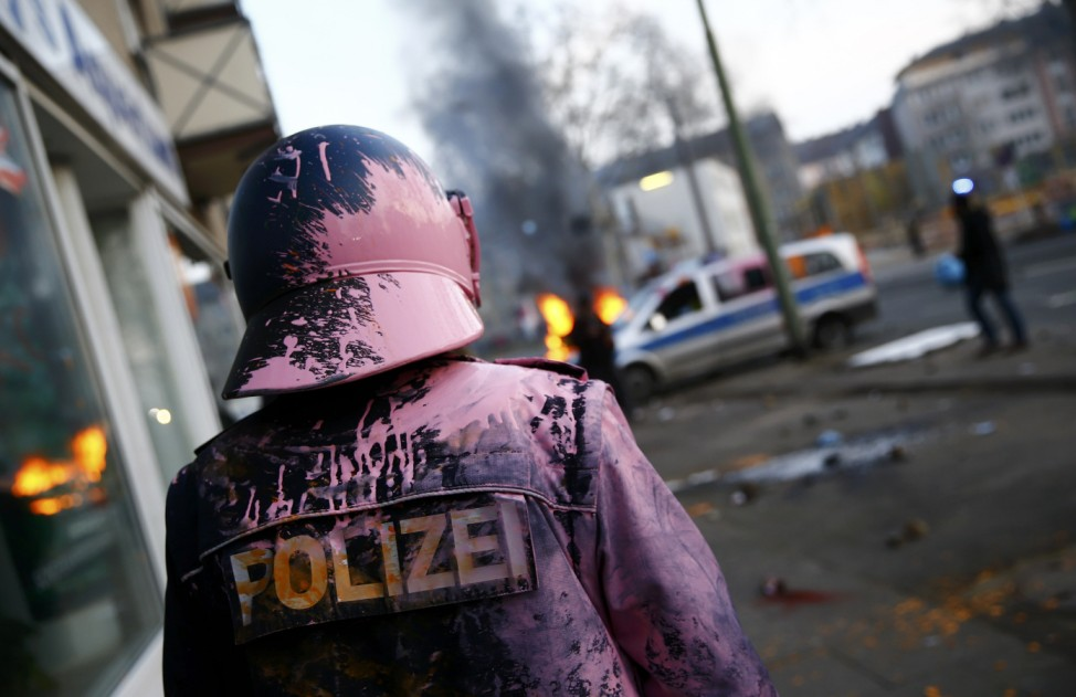 A German police officer who was hit by a paint bomb by anti-capitalist protesters looks at a burning police car near the new ECB headquarters in downtown Frankfurt
