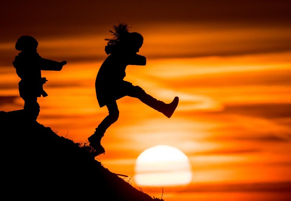Kinder spielen im Sonnenuntergang