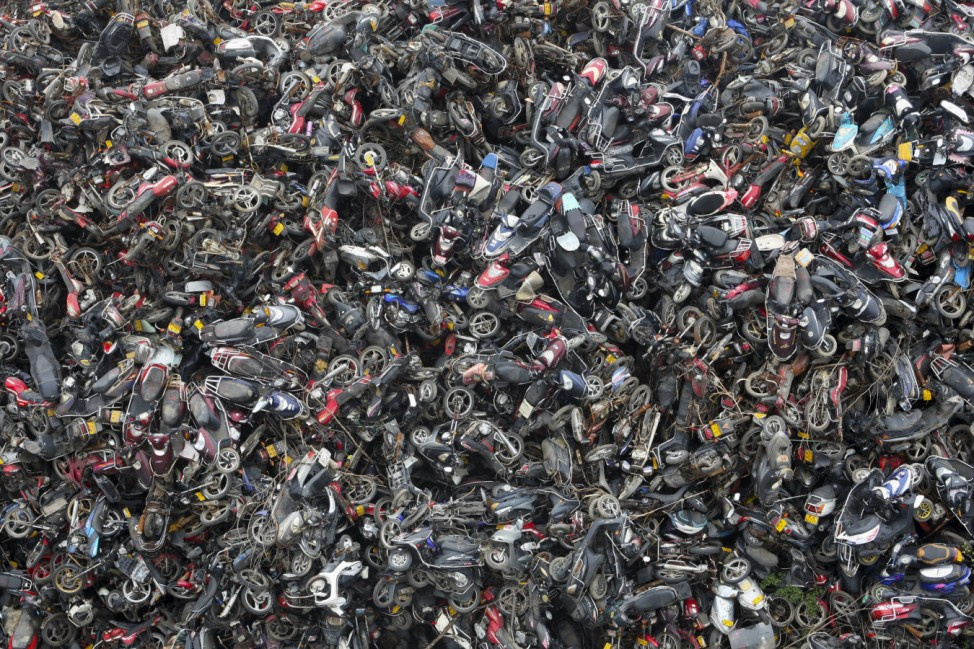 Scrapped motorbikes are piled up at a parking lot used as a scrapyard in Hangzhou, Zhejiang province