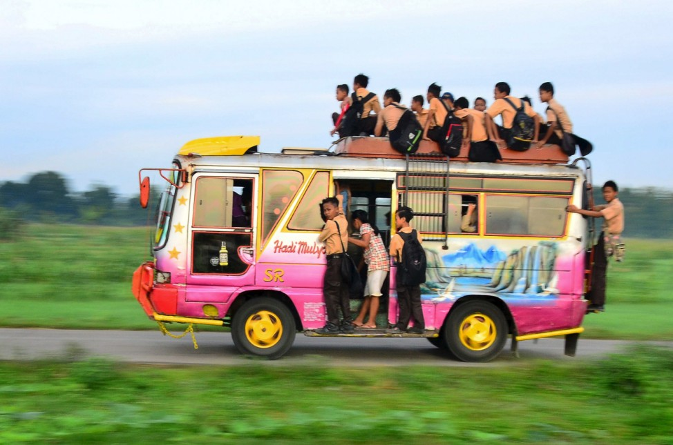 Group of students sit on top of a bus at Kemusu street in Boyolali