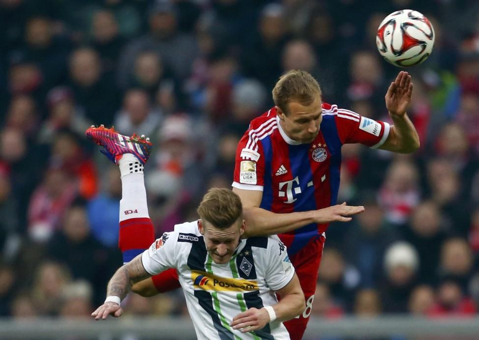 Munich's Badstuber is challenged by Moenchengladbach's Hahn during their Bundesliga first division soccer match in Munich