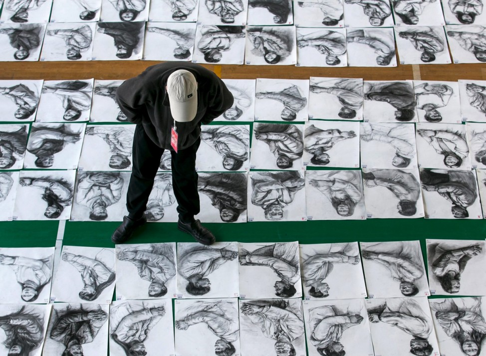 A teacher looks at sketches done by candidates taking part in an entrance examination at China Academy of Art in Hangzhou
