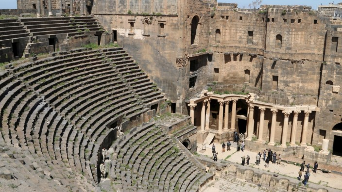 Rebel fighters walk inside a 2nd century Roman amphitheater in the historic Syrian southern town of Bosra al-Sham, after they took control of the area