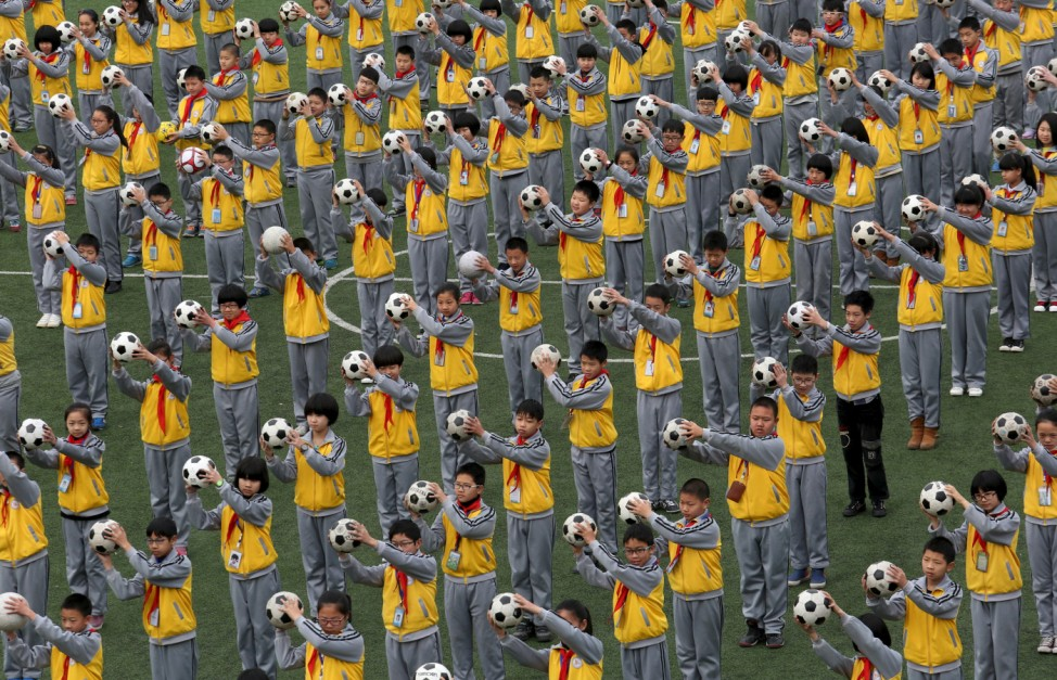 Students do morning exercises with soccer balls on a playground at a primary school in Linhai