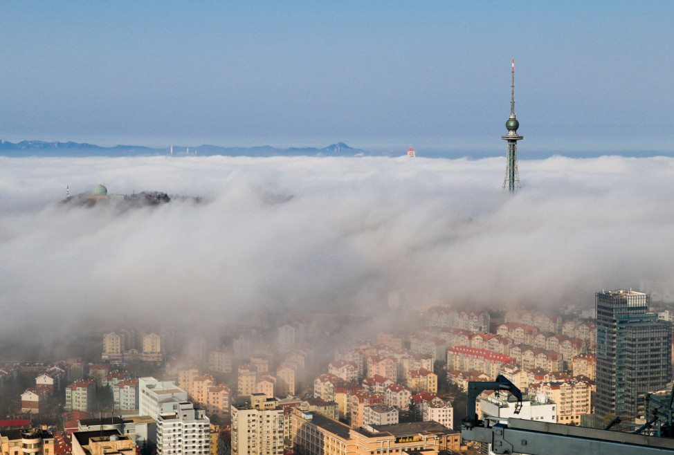Residential buildings are seen among fog in Qingdao