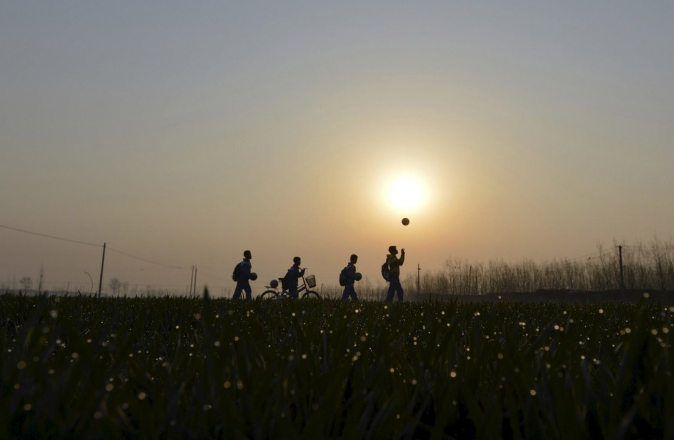 Students play with their soccer balls as they walk among crop fields to the Sunji Township Centre Primary School during sunrise in Sunji township of Shanghe county