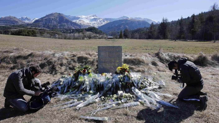 TV cameramen film at the memorial for the victims of the air disaster in the village of Le Vernet, near the crash site of the Airbus A320 in French Alps
