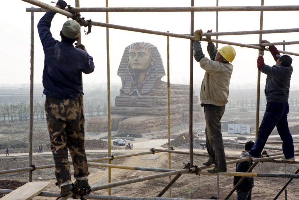 Labourers work on scaffolding near a full-scale replica of the Sphinx at an unfinished movie and animation tourism theme park, in Chuzhou