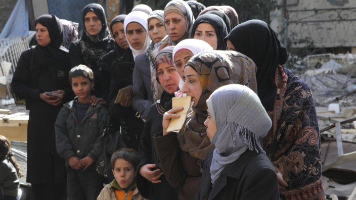 People wait to collect food aid distributed by UNRWA at the Yarmouk refugee camp