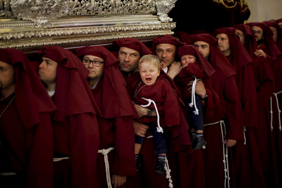 Nacho and Asier cry as they are carried by their father and uncle, who are twins, while lifting a float inside a church as they take part as penitents in the 'Salud' brotherhood in Malaga