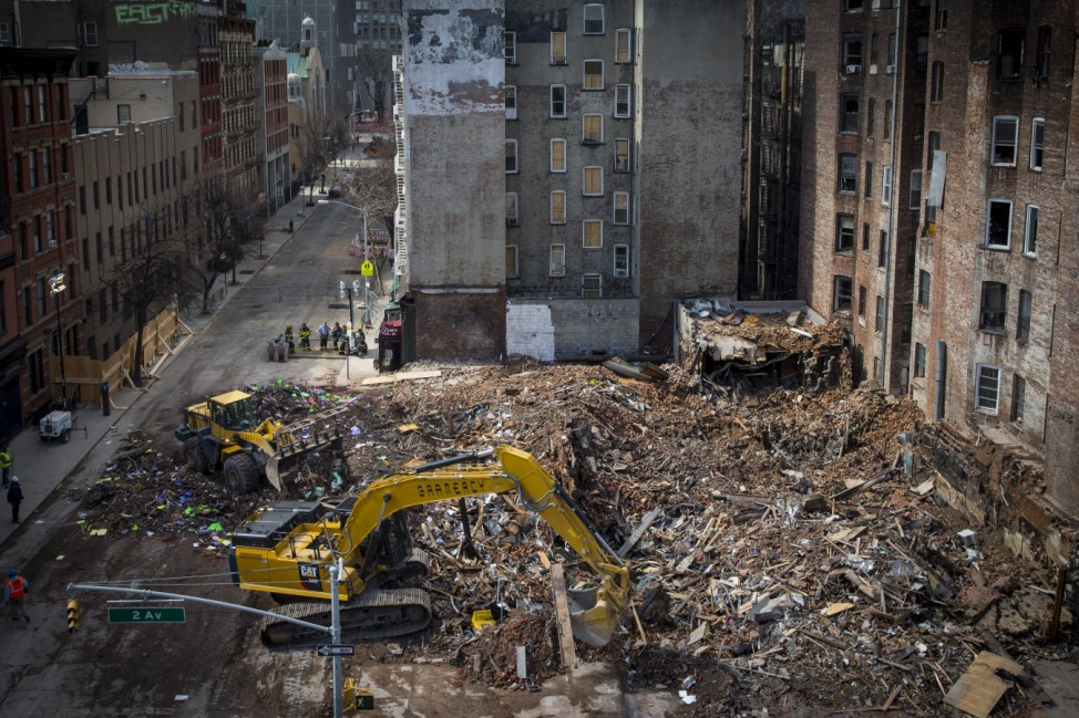 Crews remove debris at the site of a multi-building collapse on 2nd Avenue in New York
