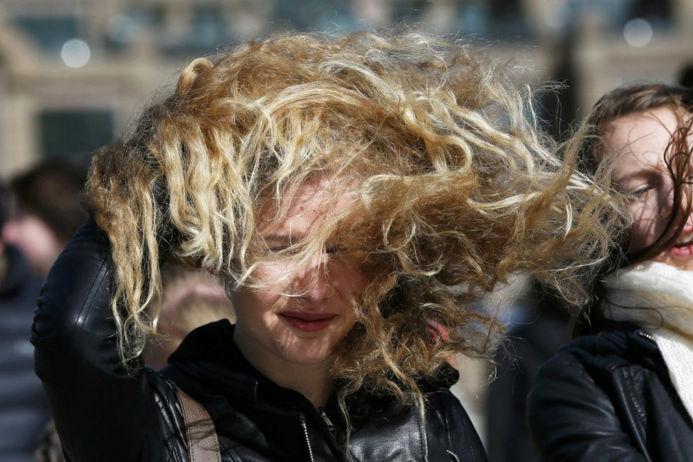 A pedestrian crosses the Millennium Bridge during strong winds in London