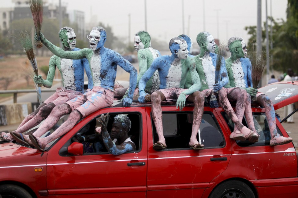 Supporters with painted bodies sit on a vehicle as they celebrate outside the office of the All Progressives Congress (APC) party after president-elect Muhammadu Buhari won the presidential election, along a street in the capital Abuja