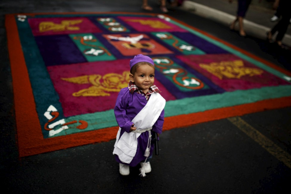 A child dressed as a member of El Jesus Nazareno participate in the 'Via Crucis' (Way of the Cross), as part of the Holy Week celebrations in the town of Izalco