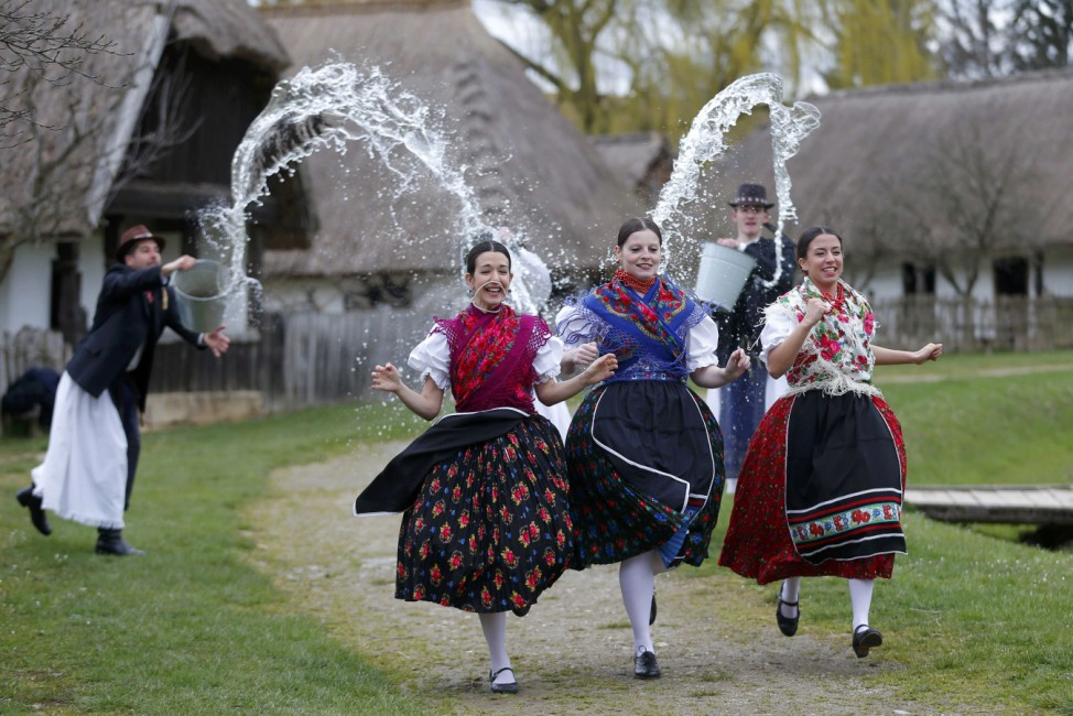 Women run as men throw water at them as part of traditional Easter celebrations, during a media presentation in Szenna