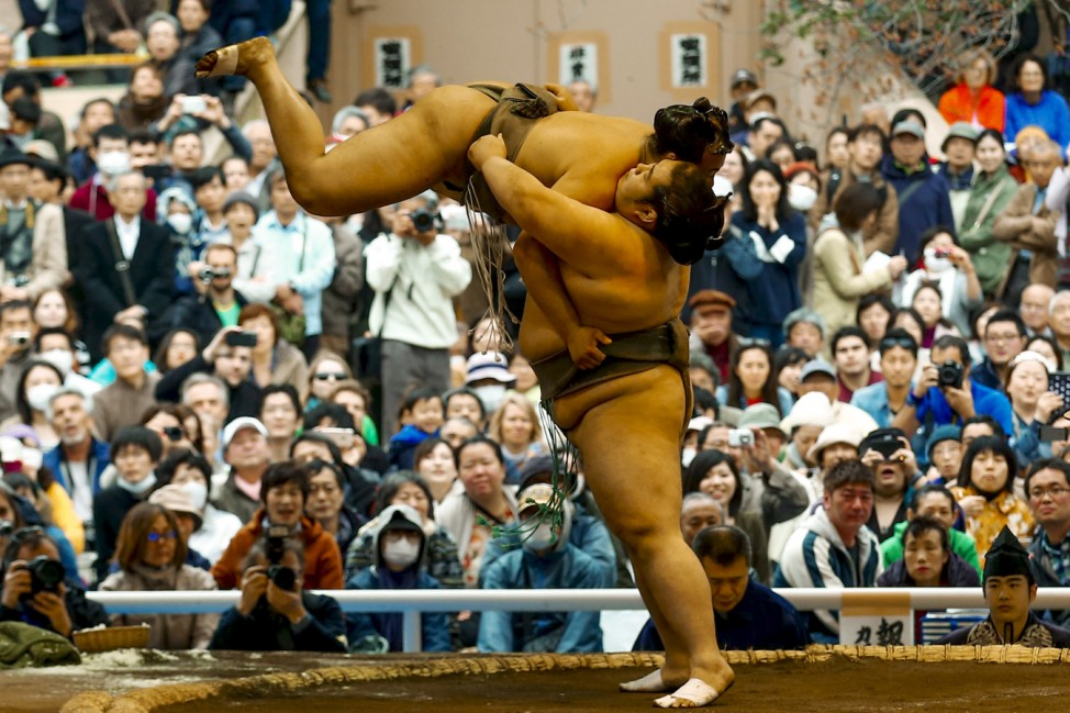 Sumo wrestlers perform a show fight during the 'Honozumo' ceremonial sumo tournament at the Yasukuni Shrine in Tokyo