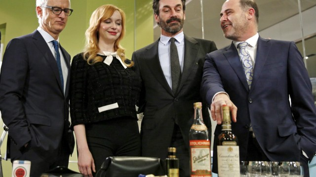 'Mad Men' stars look down as series creator Weiner places his hand on a liquor bottle during a donation ceremony at the Smithsonian National Museum of American History in Washington