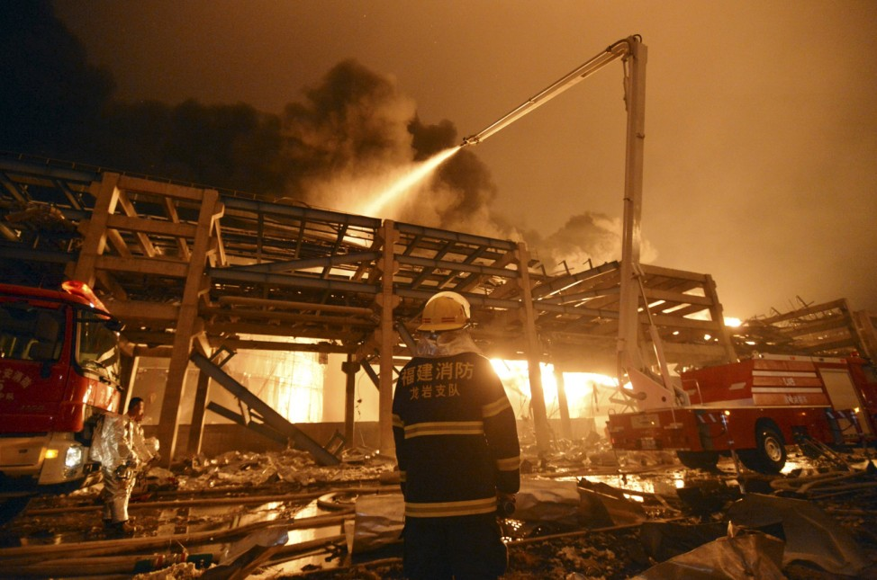 A firefighter looks on as he and his colleagues try to extinguish a fire at a petrochemical plant in Zhangzhou