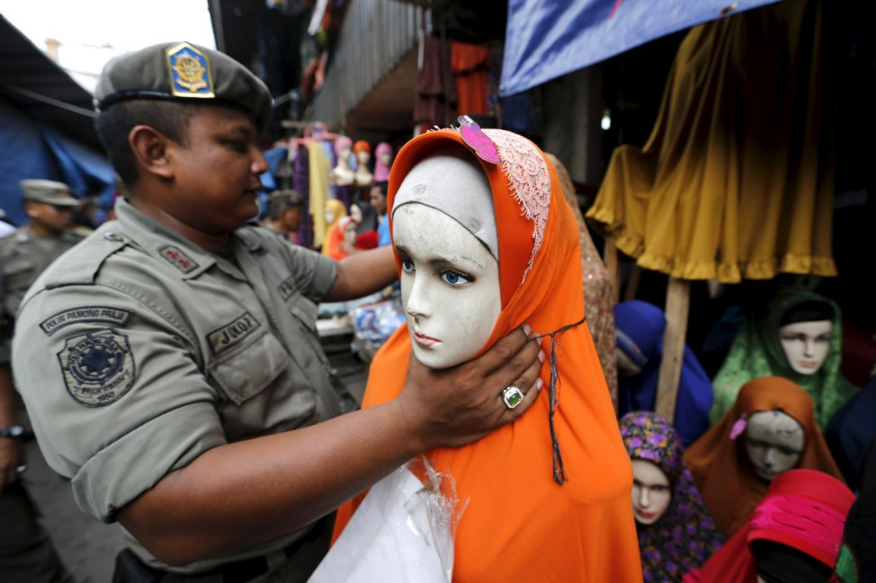 Civil Service policeman moves manequin belonging to hijab vendor during sweep operation against illegal steet vendors causing traffic congestion in Jakarta
